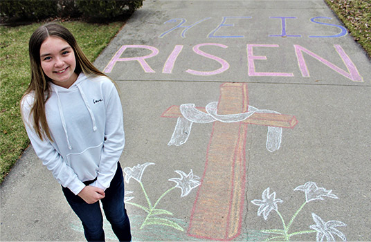 Gina Bellin, 12, of Neenah, Wis. stands beside her chalk drawing March 31, 2020, during the coronavirus pandemic.