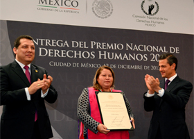 Norma Romero Vasquez receives applause from Mexico's President Enrique Pena Nieto, right, and Raul Plascencia, president of the National Human Rights Commission, after she was presented the 2013 National Human Rights Award in Mexico City Dec. 12. Romero leads a group of women known as Las Patronas, who feed Central American migrants traveling through Mexico atop northbound trains. (CNS photo) (Dec. 13, 2013)