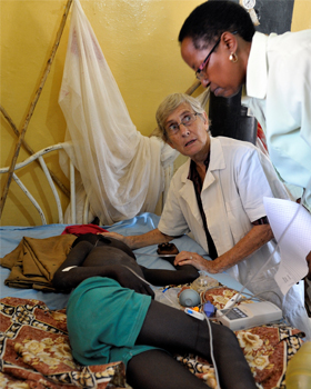 Sister Dorothy Dickson, center, a member of Sisters of Our Lady of the Missions, consults with another nurse in 2012 as she attends to a boy suffering from malaria in the Wau Teaching Hospital in Wau, South Sudan. The sick, their caregivers and any Catho lic who prays for or lovingly assists someone who is ill can gain an indulgence with prayers and service on or around the feast of Our Lady of Lourdes, which the Catholic Church marks as World Day of the Sick, Feb. 11. (CNS photo/Paul Jeffrey)