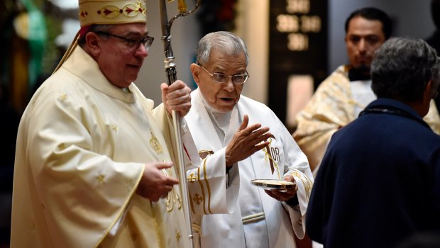Bishop Michael Olson stands next to Father Stephen Jasso, TOR, on Dec. 15, 2017 at All Saints Catholic Church in Fort Worth as they prepare to distribute Communion. (NTC/Ben Torres)