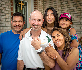Father Christopher Wadelton of Indianapolis poses for a photo with Rebeca Barcenas, right, and her family in this undated photo. Also pictured are Rebeca's husband, Rafael Ventura and the couple's two daughters, Jennifer and Carmen. (CNS photo/D. Todd Moore, courtesy The Criterion)