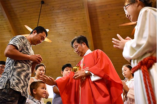 Mingee Jang, left, and his children receive Communion and a blessing from Father Woon Pil Jeong during a special Mass celebrating the Feast of the Korean Martyrs Sept. 22 at Korean Martyrs Catholic Church in Hurst. (NTC/Ben Torres)