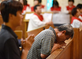 Yue Kwang Yoon, left, and Chang Yung Kang kneel for prayer before receiving Communion during a special Mass celebrating the Feast of the Korean Martyrs Sept. 22 at Korean Martyrs Parish in Hurst. (NTC/Ben Torres)