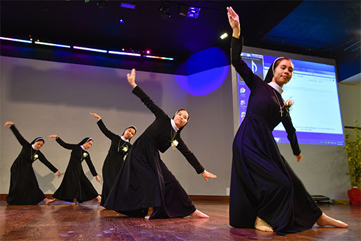 A group of sisters from the Lovers of the Holy Cross religious order perform a special dance after renewing their vows at Vietnamese Martyrs Parish in Arlington. (NTC/Ben Torres)