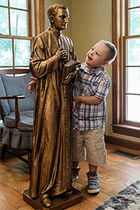 Mikey Schachle, 5, examines a statue of Father Michael McGivney at the home where he lives with his parents, Daniel and Michelle, and siblings in Dickson, Tenn., June 2, 2020. (CNS photo/Rick Musacchio, Tennessee Register)