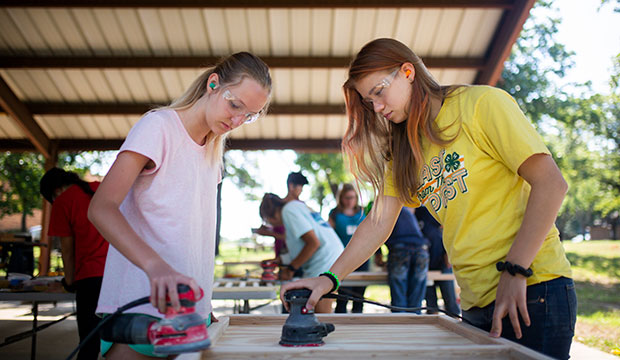 Lauren Wilde and Annice Barber-Petroff sand a part for a baby bed as they take part in the Metanoia Retreat at Saint Ann Parish in Burleson, Sunday, July 21, 2019.
