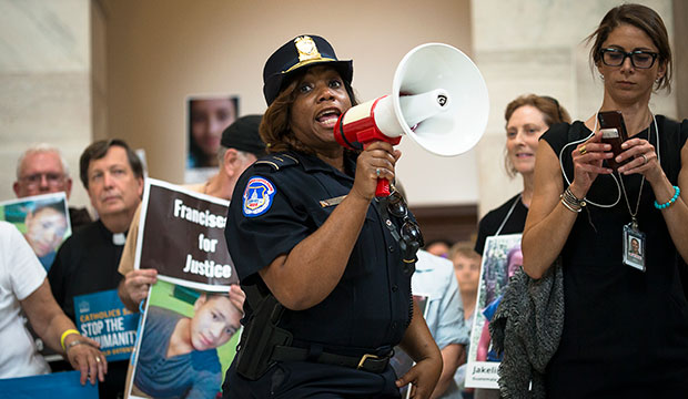 "A Capitol Police officer warns demonstrators of their potential arrest July 18, 2019, during a ""Catholic Day of Action for Immigrant Children"" at the Russell Senate Office Building in Washington. (CNS photo/Tyler Orsburn)"