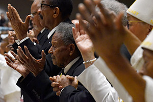 Members of the Knights of Peter Claver and its Ladies Auxiliary raise their hands in prayer during the annual Dr. Martin Luther King, Jr. Diocesan Memorial Mass  Jan. 11 at St. Joseph Roman Parish in Arlington. (NTC/Ben Torres)