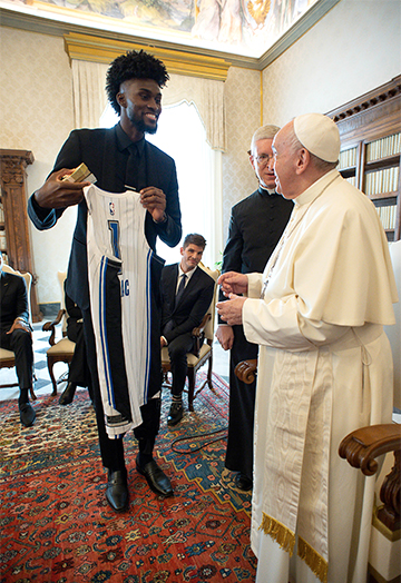 Jonathan Isaac of the Orlando Magic presents a jersey with his number to Pope Francis during a meeting with a delegation from the National Basketball Players Association at the Vatican Nov. 23, 2020. (CNS photo/Vatican Media)