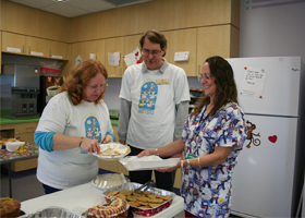 Cherie Haefner and her husband, Leland, serve oncology nurse Kathleen Gordon a warm meal courtesy of Noreen's Nourishment.