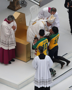 Pope Francis blesses a family of four during the offertory as he celebrates the closing Mass of World Youth Day on Copacabana beach in Rio de Janeiro July 28. (CNS photo/Sergio Moraes, Reuters)
