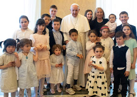 Pope Francis poses during an audience with a delegation from the Institute of the Innocents, a Florence-based organization dedicated to caring for children.