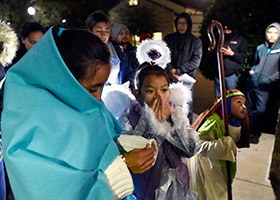 Maria Figueroa, dressed as Mary; Izabella Bun, dressed as an angel; and Dominic Perches, dressed as Joseph; stand outside in cold temperatures during a Posada celebration at Immaculate Conception Church in Denton, Dec. 17. (NTC/Ben Torres)