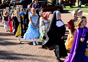 Children dressed in saints costumes participate in the St. Peter Parish procession on Oct. 27