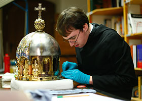 Restorer Luke Jonathan Koeppe cleans part of the shrine with the relics of St. Corona at the cathedral in Aachen, Germany, March 25, 2020, amid the coronavirus pandemic. (CNS photo/Thilo Schmuelgen, Reuters)