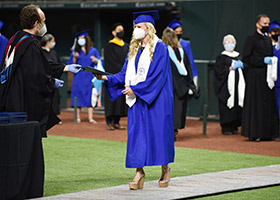 A Nolan graduate receives her diploma at Globe Life Field on July 11