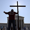 A man stands with a cross in front of the Supreme Court