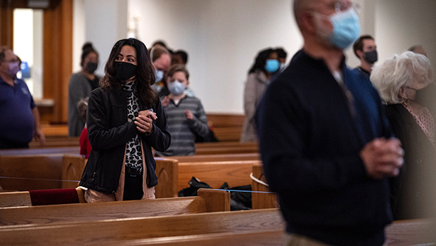 A member of the Guardian Ministry, stands for prayer while watching parishioners during Sunday Mass at St. Thomas the Apostle Catholic Parish in Fort Worth Nov. 29, 2020.