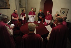 "Italian Cardinal Tarcisio Bertone, center with red skull cap, prays with assistants as the ceremonies and tasks of the ""sede vacante"" begin at the Vatican Feb. 28. The red velvet-covered scepter before him is the symbol of his authority as camerlengo or chamberlain. He is charged with administering the temporal goods of the church following the resignation of Pope Benedict XVI. (CNS photo/L'Osservatore Romano via Catholic Press Photo)"