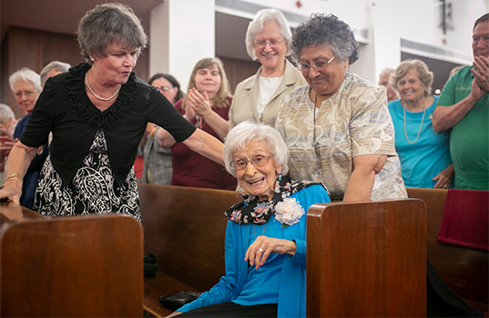 Sister Mary Frances Serafino, SSMN, is applauded by her friend Pat Walsh, of Norfolk, Virginia (left) and Sister Dorothy Powers and Sister Gabriela Martinez at a jubilee Mass celebrating her 70 years of consecrated life Sept. 28 at Holy Family Parish in Fort Worth. Sister Mary Frances died Sept. 9, 2020. (NTC/Rodger Mallison)