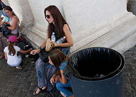 A woman holds water bottles next to a trash can under the St. Peter's Square colonnade at the Vatican July 16, 2019. A Vatican official said the Vatican is collecting 22 pounds of plastic a day from trash containers under the colonnade.