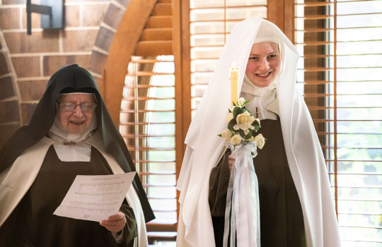 Sister Mary Francisca (right) smiles toward her family and friends after her investiture and a Mass concelebrated by Bishop Michael Olson and seven other priest at the Arlington Carmel. (NTC/Juan Guajardo)