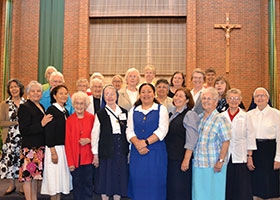 Sister Lola Ulupano (center) is shown with members of her religious order community after her profession of solemn vows on Aug. 10 at St. Michael Parish in Bedford. (Courtesy photo)