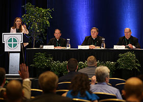 Judy M. Keane, director of the U.S. Conference of Catholic Bishops' Office of Public Affairs, calls on a reporter during a news conference June 13, 2019, at the spring general assembly of the U.S. Conference of Catholic Bishops in Baltimore. Pictured on the press panel are Bishop Michael F. Burbidge of Arlington, Va., Cardinal Joseph W. Tobin of Newark, N.J., and Bishop Robert P. Deeley of Portland, Maine. (CNS photo/Bob Roller)