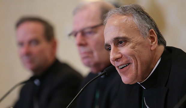 Cardinal Daniel N. DiNardo of Galveston-Houston, president of the U.S. Conference of Catholic Bishops, smiles during a news conference on the first day of the spring general assembly of the USCCB in Baltimore June 11, 2019. Also pictured are Bishop Michael F. Burbidge of Arlington, Va., and Bishop Robert P. Deeley of Portland, Maine. (CNS photo/Bob Roller)
