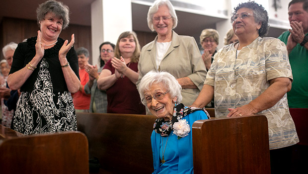 Sister Mary Frances Serafino, SSMN, is applauded by her friend Pat Walsh, of Norfolk, Virginia (left) and Sister Dorothy Powers and Sister Gabriela Martinez at a jubilee Mass celebrating her 70 years of consecrated life Sept. 28 at Holy Family Parish in Fort Worth. (NTC/Rodger Mallison)
