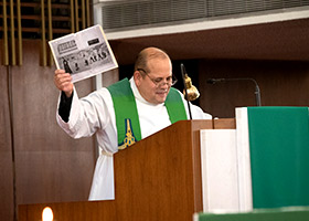 Father Richard Flores delivers the homily and shows a picture of Sister Mary Frances Serafino from her days as a football coach, during a jubilee Mass at Holy Family Church Sept. 28. (NTC/Rodger Mallison)