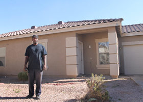 Terrance Alston poses in early November 2013 in front of a vacant house he helped renovate in Chandler, Ariz. He is one of 925 client success stories St. Joseph the Worker social service agnecy could tell from helping homeless clients regain self-suffici ency. (CNS photo/Ambria Hammel, Catholic Sun)