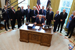 President Donald Trump signs the $2.2 trillion coronavirus aid package bill in the Oval Office of the White House March 27, 2020. (CNS photo/Jonathan Ernst, Reuters)