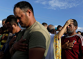 A priest blesses a man during an outdoor Mass in Pacaraima, Brazil, after his group was denied entrance to Venezuela Feb. 22, 2019. Venezuelan President Nicolas Maduro closed the border between the two countries Feb. 21. (CNS photo/Ricardo Moraes, Reuters) See VENEZUELA-BRAZIL-BORDER Feb. 25, 2019.