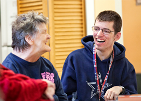 Volunteer Trevor Lanham, right, laughs with resident Linda Sollers at the Crofton Care and Rehabilitation Center during an activity in early December in Crofton, Md. The 26-year-old, who is mentally disabled, volunteers at the nursing home three afternoo ns a week, often assisting the staff with entertainment and activities. (CNS photo/Tom McCarthy Jr., Catholic Review)