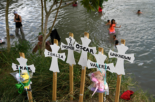 Migrants in Tamaulipas, Mexico, bathe in the Rio Grande Oct. 7, 2019, near a makeshift memorial honoring the lives of fellow migrants who have died on their journey north. (CNS photo/Loren Elliott, Reuters)