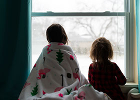 two girls look out at a winterscape