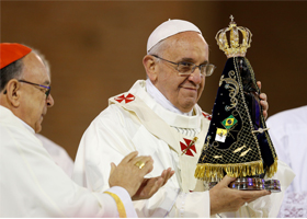 Pope Francis holds up a statue of Our Lady of Aparecida after it was presented to him by Cardinal Raymundo Damasceno Assis of Aparecida, left, at the beginning of Mass at the Basilica of the National Shrine of Our Lady of Aparecida July 24. (CNS photo/Paul Haring)